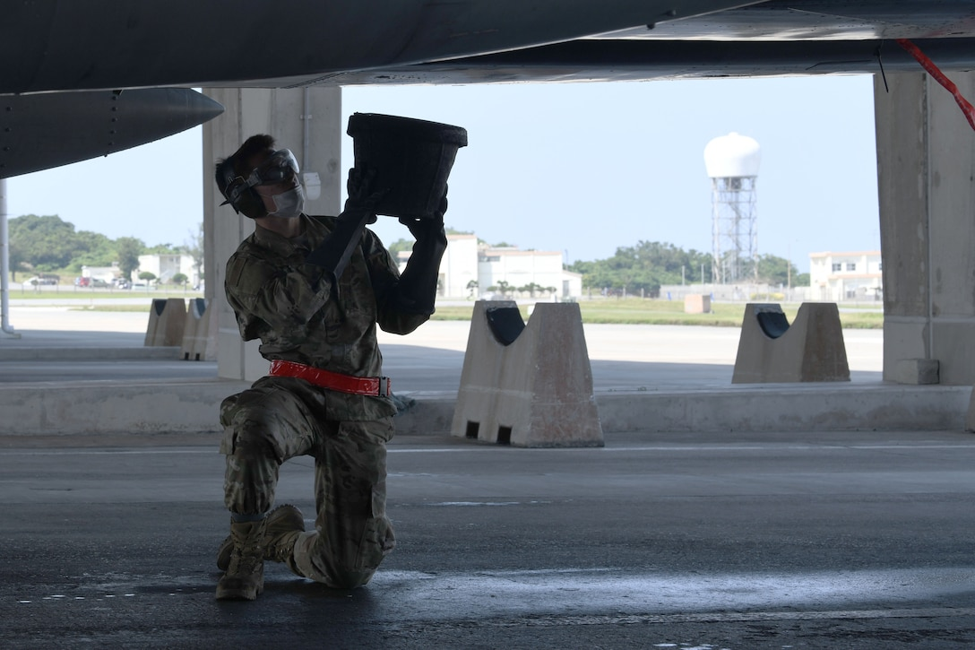 Airman 1st Class Jacob Boyer, avionics technician from the 67th Aircraft Maintenance Unit, collects discharged water from an F-15C Eagle. In order to ensure mission success, the Airmen of Team Kadena continuously rise to meet mission requirements and ensure air superiority. (U.S. Air Force photo by Airman 1st Class Rebeckah Medeiros)