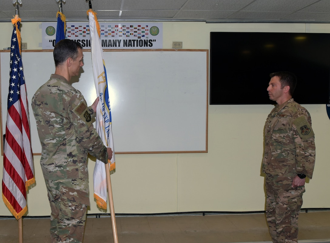 From left, Maj. Gen. Alexus G. Grynkewich, the outgoing 9th Air Expeditionary Task Force-Levant commander, passes the task force guidon to Chief Master Sgt. Antonio Goldstrom, 9 AETF-L command chief during the 9 AETF-L Change of Command at Camp Arifjan, Kuwait, April 20, 2020.