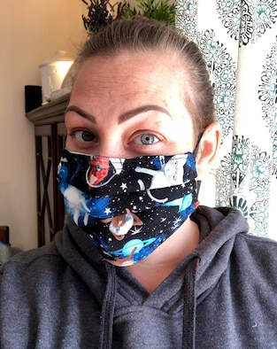Katie Robertson, Mildenhall Spouses Association member, poses for a photo while wearing a protective mask she made at her home, April 15, 2020. The fabric used for each mask falls within guidelines of the Department of Defense color restrictions and mirrors the Centers for Disease Control's instructions on how protective face masks should be made to protect individuals from COVID-19. (Courtesy photo)