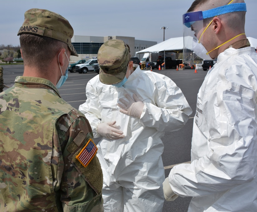 Several Soldiers from the Pennsylvania National Guard go through the procedures of sealing a suit during practice for COVID-19 testing at Mohegan Sun Arena in Wilkes-Barre, Pa., on April 19, 2020. The Pa. National Guard Soldiers are supporting the Department of Health's operation to stand up a testing site to assist the community. (U.S. Army photo by Sgt. 1st Class Matthew Keeler)