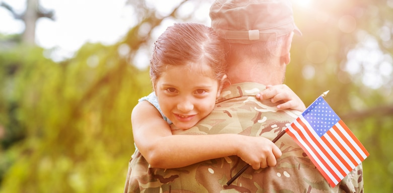 photo shows a young girl hugging her father who is in a military uniform while she is holding an American flag.