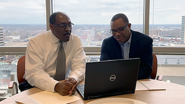 Two men conduct a training webinar.