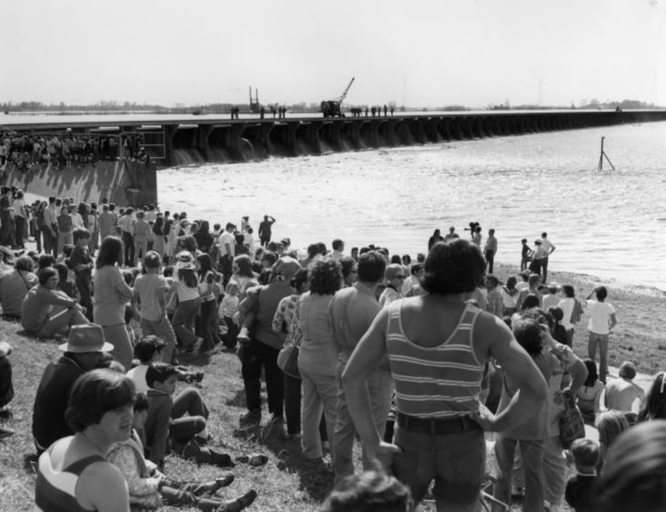 View of crowds on shore watching opening of Spillway in the background.