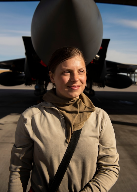 U.S. Air Force Airman 1st Class Kristin Lyons, 391st Fighter Squadron crew chief, stands by an F-15E Strike Eagle at the end of a 12-hour shift, April 14, 2020, at Mountain Home Air Force Base, Idaho. To increase safety of Airmen during the COVID-19 pandemic, the 391st FS has divided into teams, created an adjusted schedule and implemented CDC safety measures. (U.S. Air Force photo by Airman 1st Class Andrew Kobialka)