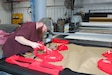Logan Robinson, Letterkenny Army Depot upholstery shop employee, cuts fabric for the production of cloth masks at Letterkenny Army Depot in Chambersburg, Pa. The masks are being produced as part of LEAD's efforts to mitigate the spread of the Coronavirus.