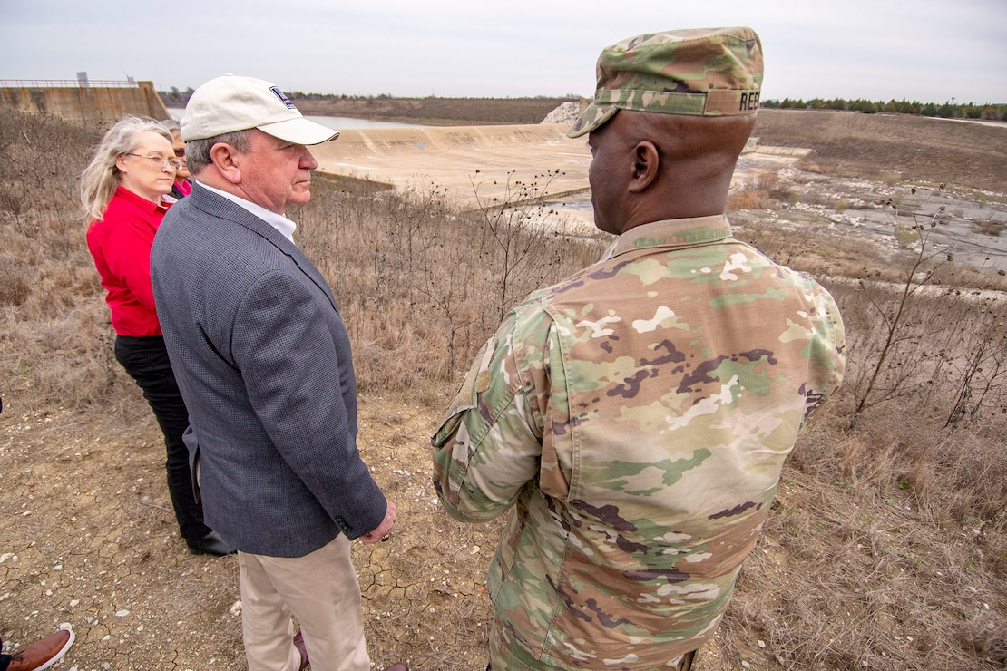 R.D. James, Assistant Secretary of the Army for Civil Works, middle, speaks with U.S. Army Corps of Engineers (USACE), Fort Worth District Commander Col. Kenneth Reed, right, and Dam Safety Project Manager Stacy Gray, left, during a visit to the Lewisville Dam Spillway. Mr. James visited Lewisville Lake to meet USACE Fort Worth staff and receive a brief of the Lewisville Dam Safety Modification and other lake projects. Fort Worth District was established in 1950. Lewisville Lake dam constructed in 1955, it has 187 miles of shoreline, 28 designated public use areas, 16,352 acres above normal pool and 5,747 acres of flowage easement. The district is responsible for water resources development in two-thirds of Texas, and design and construction at military installations in Texas and parts of Louisiana and New Mexico. U.S Army photo by Trevor Welsh.