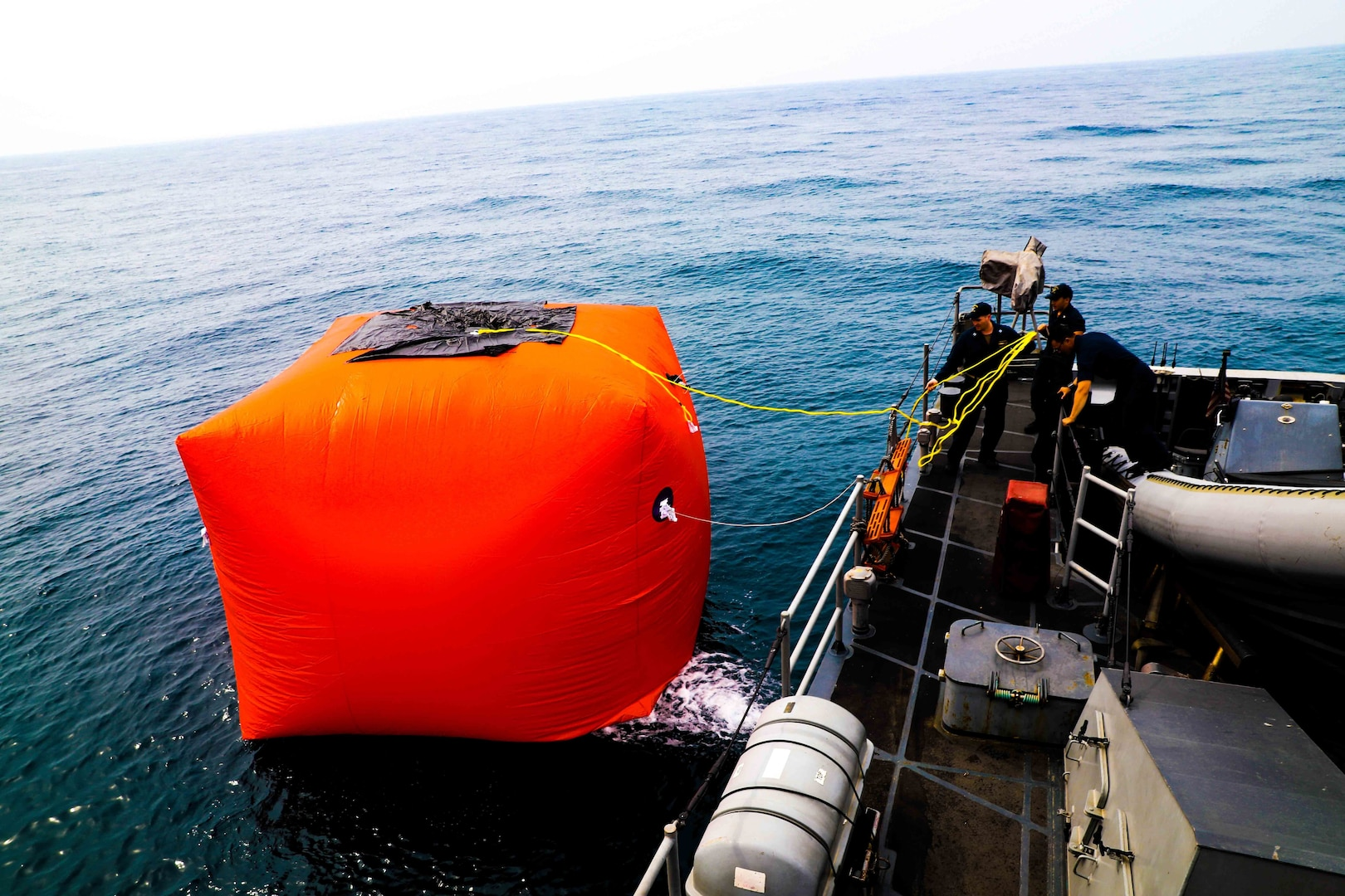 Sailors aboard the coastal patrol ship USS Sirocco (PC 6) place an inflatable target into the water during a live fire exercise with U.S. Army AH-64E Apache attack helicopter assigned to U.S. Army Central Command's (USARCENT) Task Force Saber. Sirocco is deployed to the U.S. 5th Fleet area of operations in support of naval operations to ensure maritime stability and security in the central region, connecting the Mediterranean and the Pacific through the Western Indian Ocean and three strategic choke points.