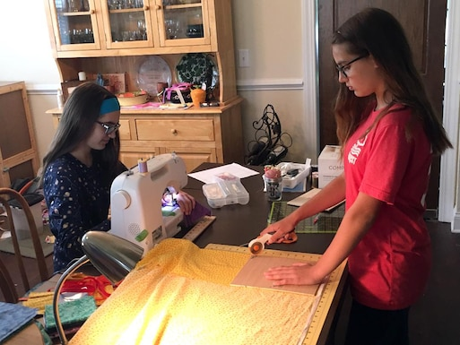 Karina, left, and Kolleen Roessig work together to make reusable cloth face masks. The sisters are making the masks to donate to help combat the spread of the coronavirus. (Courtesy photo)