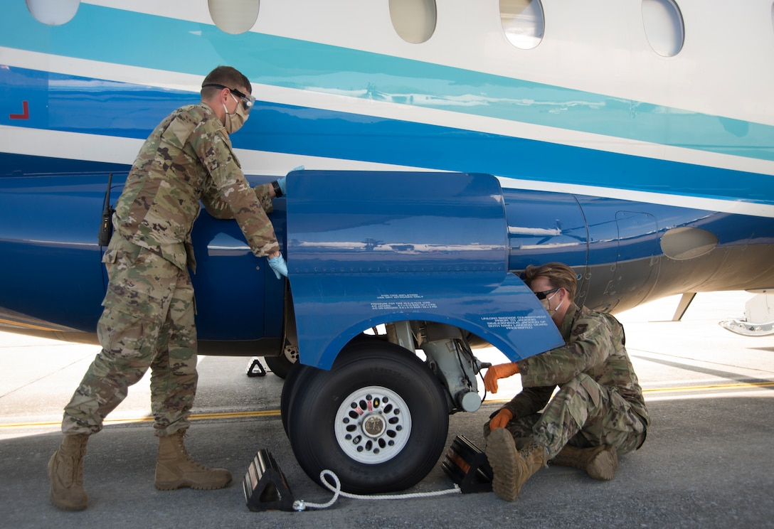 Crew chiefs inspect the wheels on a C-146A Wolfhound