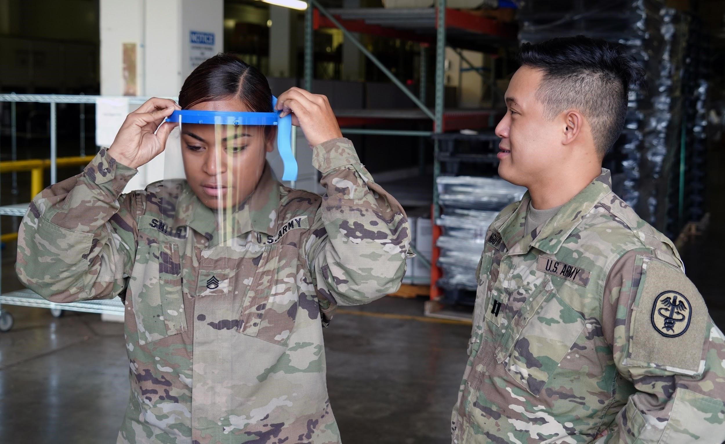 U.S. Army Staff Sgt. Jacklyn Smith, Tripler Army Medical Center medical warehouse non-commissioned officer in charge, receives assistance from U.S. Army Capt. Scott Nguyen, TAMC General Surgery resident physician, with adjusting her face shield at TAMC, Hawaii, April 3, 2020. Due to a shortage of disposable masks, the 15th Wing is using 3D printers to make face shields to donate across the island to combat the COVID-19 pandemic. (U.S. Air Force photo by Airman 1st Class Erin Baxter)
