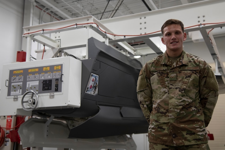A1C Benjamin Missel poses with a landing gear trainer in the F-35 Academic Training Center, Eglin Air Force Base, Fla. on Mar. 12, 2020.