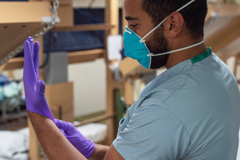 A seaman wearing hospital scrubs and a face mask puts on a pair of gloves.