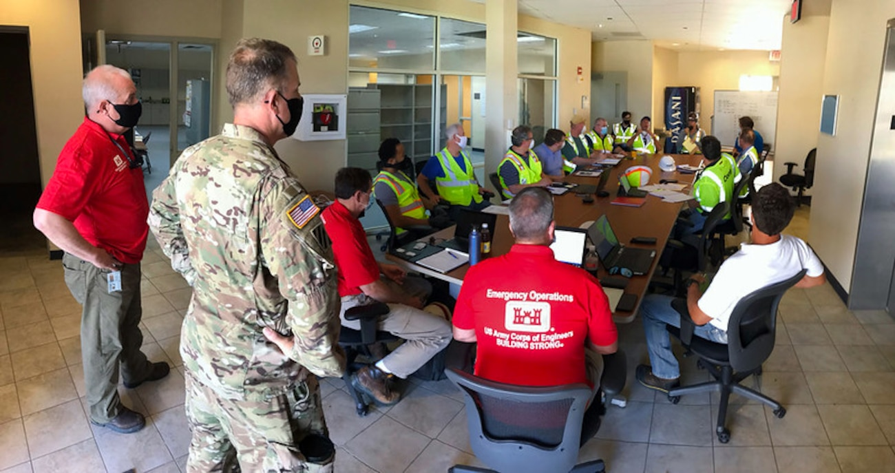 Col. Daniel Hibner (left), Savannah District Commander, and Erik Blechinger, District Deputy Engineer, address members of Conti Federal Services, Inc., the contractor converting the Regional Training Institute barracks into a alternate care facility for COVID-19 on St. Croix Island, April 20, 2020.