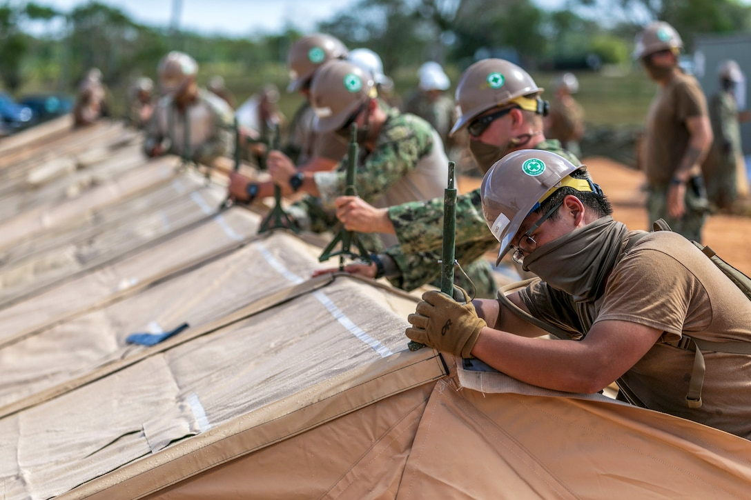 Sailors wearing hard hats and face masks work in a line on a tent.