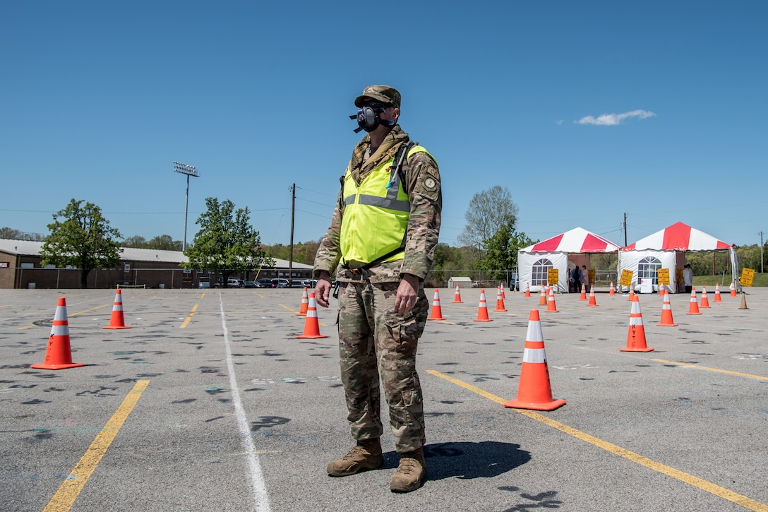 Master Sgt. Jason Michel, a security forces specialist for the Kentucky Air National Guard's 123rd Contingency Response Group, directs patients through a drive-through testing station for COVID-19 in Madisonville, Ky., April 21, 2020. Kentucky Air Guardsmen will be supporting multiple testing sites across the state. (U.S. Air National Guard photo by Staff Sgt. Joshua Horton)
