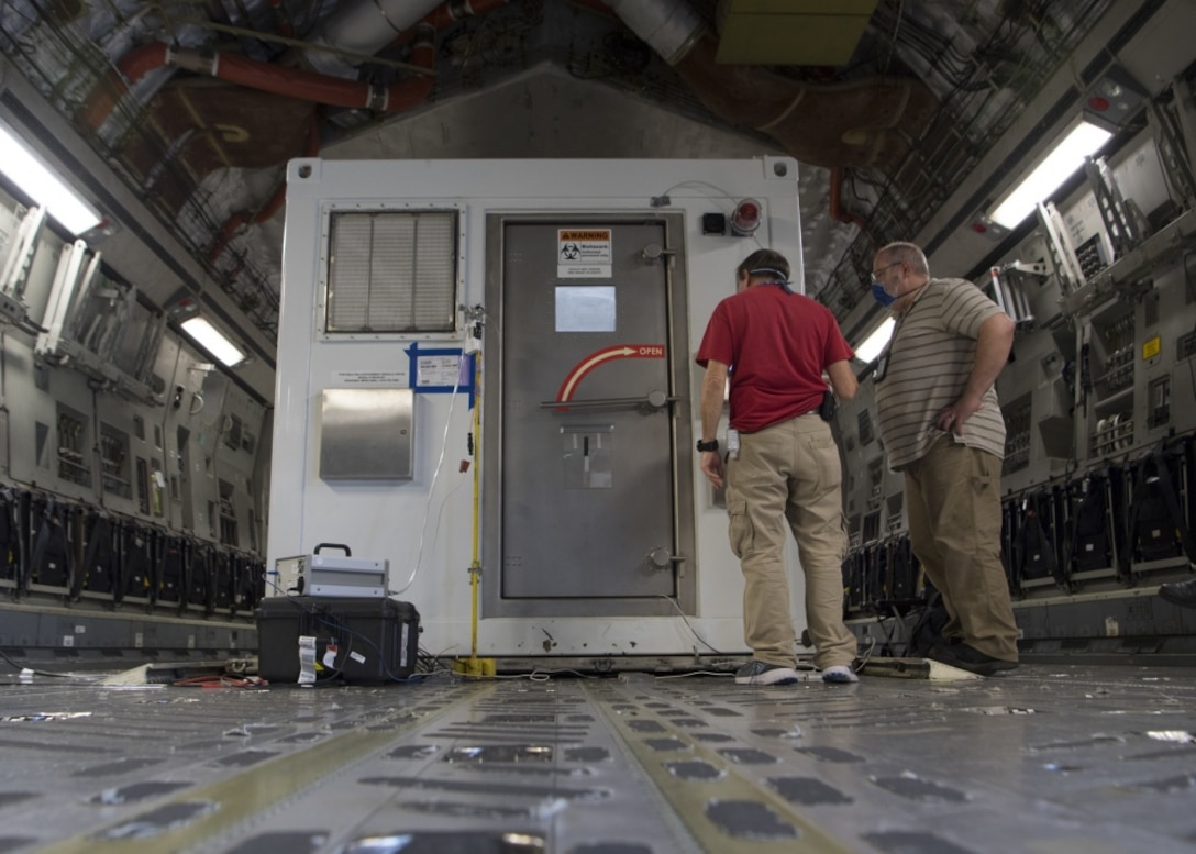 Victor Arca, 28th Test and Evaluation Squadron senior test engineer, and Gabriel Intano, Army Public Health Center microbiologist, collect data while performing testing on a Portable Bio-Containment Module loaded onto a C-17 Globemaster III at Joint Base Charleston S.C., April 15, 2020. Members from the 28th TES and Army PHC tested the PBCM, which will be exercised regularly to transport COVID patients and medical personnel, all while ensuring the aircrew is impervious to risk of infection. (U.S. Air Force photo by Staff Sgt. Chris Drzazgowski)