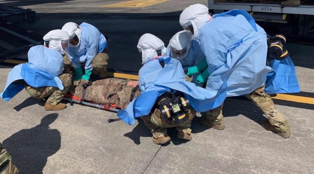 Members of the Portable Bio-Chemical Module test team prepare to load a patient.