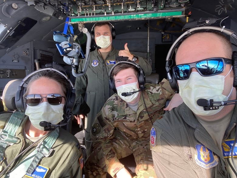crew members on a Dobbins C-130H3 Hercules pose for a photo wearing masks on April 5, 2020. They transported five Air Force Reserve medical personnel to Joint Base McGuire-Dix-Lakehurst, New Jersey, to join the effort in combating COVID-19 in New York City. The Dobbins C-130H also made stops at MacDill Air Force Base and Patrick AFB in Florida, and Charleston AFB, South Carolina to pick up more Reserve Citizen Airmen to join the fight. Pictured from left to right, clockwise, are Capt. Latessa Meader, co-pilot; Maj. Jonathan Bonde, navigator; Tech. Sgt. Joey Burnett, flight engineer; and Maj. Brian Metzger, aircraft commander