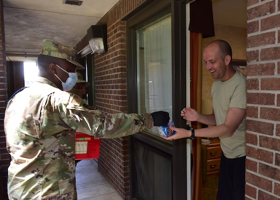 U.S. Air Force Tech. Sgt. Abram Robins, 17th Training Wing military training leader, delivers a care package to an airman in isolation on Goodfellow Air Force Base, Texas, April 20, 2020. The care packages are part of an ongoing joint project between the base and local civic leaders to ensure inbound members are taken care of during their mandatory isolation period as a result of the COVID-19 pandemic. (U.S. Air Force photo by Staff Sgt. Chad Warren)