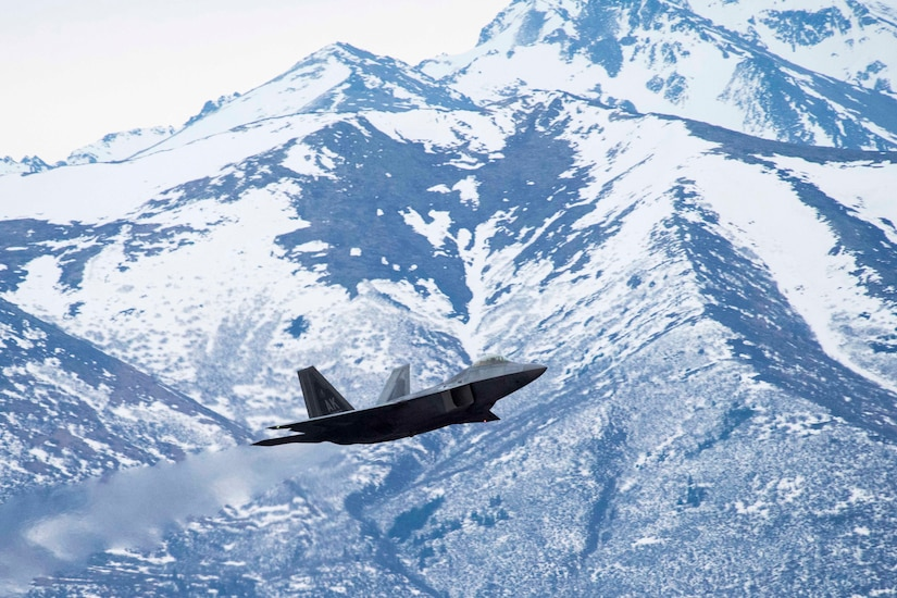 A military aircraft flies in front of snow-covered mountains.