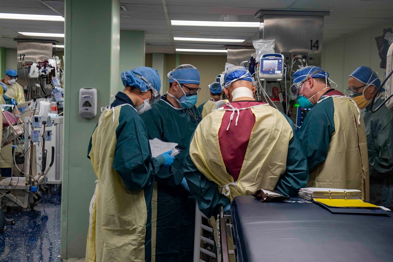 Multiple personnel in hospital scrubs confer with each other in a medical facility.