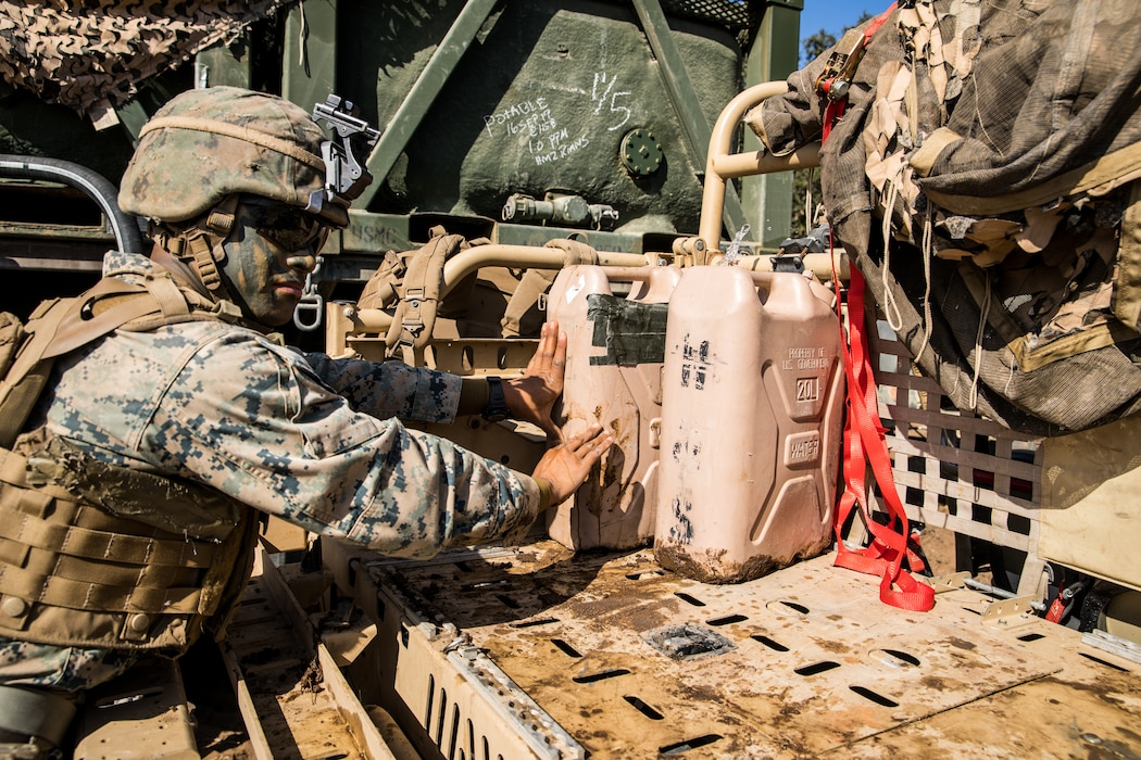 U.S. Marine Corps Lance Cpl. Joseph Sison, a rifleman with 1st Battalion, 5th Marine Regiment, 1st Marine Division, pushes water jugs onto a vehicle during the Marine Corps Combat Readiness Evaluation (MCCRE) on Marine Corps Base Camp Pendleton, California, Sept. 17, 2019. 5th Marines conducted a regimental-sized MCCRE that included 1st Battalion, 5th Marines, 2nd Battalion, 5th Marines, and the Regimental Headquarters to increase the combat proficiency and readiness of the regiment. The MCCRE took place over a 10-day period and served as a proof of concept for future regimental-sized MCCREs. (U.S. Marine Corps photo by Lance Cpl. Alexa M. Hernandez)