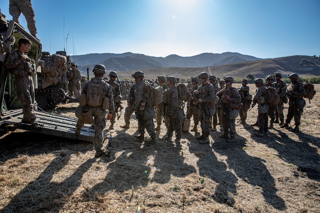 U.S. Marines with 2nd Battalion, 5th Marine Regiment, 1st Marine Division,  prepare to enter an assault amphibious vehicle during a Marine Corps Combat Readiness Evaluation (MCCRE) on Marine Corps Base Camp Pendleton, California, Sept. 23, 2019. 5th Marines conducted a regimental-sized MCCRE for 1st Battalion, 5th Marines and 2nd Battalion, 5th Marines, as well as the Regimental Headquarters to increase the combat proficiency and readiness of the regiment. The MCCRE took place over a 10 day period and served as proof of concept for future regimental-sized MCCREs. (U.S. Marine Corps photo by Lance Cpl. Roxanna Ortiz)