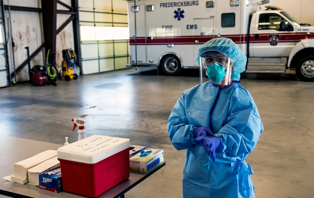A Texas Air National Guard medic, attached to the 149th Fighter Wing, prepares to receive patients by properly securing her personal protective equipment at a community-based testing facility in Fredericksburg, Texas, April 19, 2020. The Texas Military Department, in tandem with state partners, has established community-based testing facilities to provide drive-in COVID-19 screenings to communities not served by a county health department. These facilities will allow Texas to curb the spread of COVID-19. (U.S. Army National Guard photo by Charles E. Spirtos)
