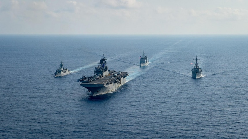 Royal Australian Navy guided-missile frigate HMAS Parramatta (FFH 154), left, sails with U.S. Navy Amphibious assault ship USS America (LHA 6), Ticonderoga-class guided-missile cruiser USS Bunker Hill (CG 52) and Arleigh-Burke class guided missile destroyer USS Barry (DDG 52). Bunker Hill is deployed to the U.S. 7th Fleet area of operations and is operating with the America Expeditionary Strike Group in support of security and stability in the Indo-Pacific region.