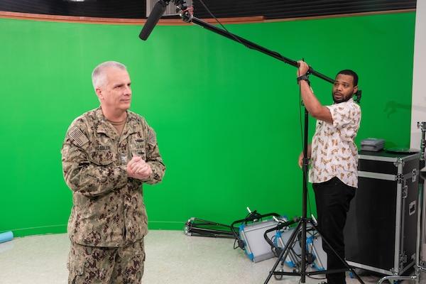 Code 1170 Videographer Alim Jordan sets up the microphone for Deputy Shipyard Commander Capt. Dan Rossler before he films a video regarding tips for minimizing the spread of COVID-19.