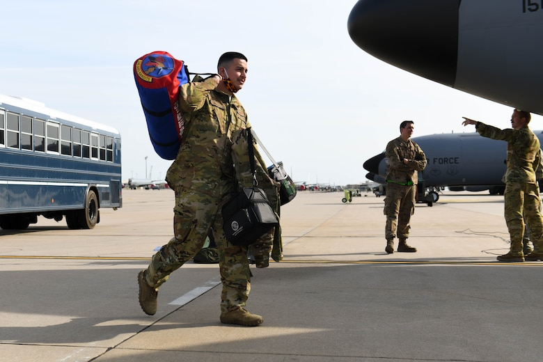 Senior Airman Joshua Granados, 349th Air Refueling Squadron boom operator, carries his personal belongings to a KC-135 Stratotanker Apr. 9, 2020, at McConnell Air Force Base, Kansas. In order to support ongoing air refueling operations, each aircraft was assigned a second augmented aircrew to take over operation of the aircraft during the second half of the flight to Qatar. (U.S. Air Force photo by Airman 1st Class Nilsa E. Garcia)
