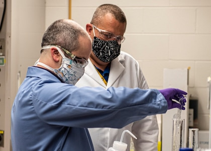 Jeff Eichler, left, and Dr. Josh Kogot, right, work to produce batches of hand sanitizer to be used by Naval Surface Warfare Center Panama City Division personnel to combat COVID-19.