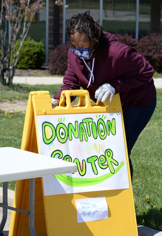 Bernadette Worsham, 88th Air Base Wing donation coordinator, sets up a sign for the 88th Air Base Wing's donation drop off point outside the chapel located in the Prairies housing area at Wright-Patterson Air Force Base, Ohio, April 21, 2020. The center is open Monday-Friday between 1 and 5 p.m. (U.S. Air Force photo/Wesley Farnsworth)