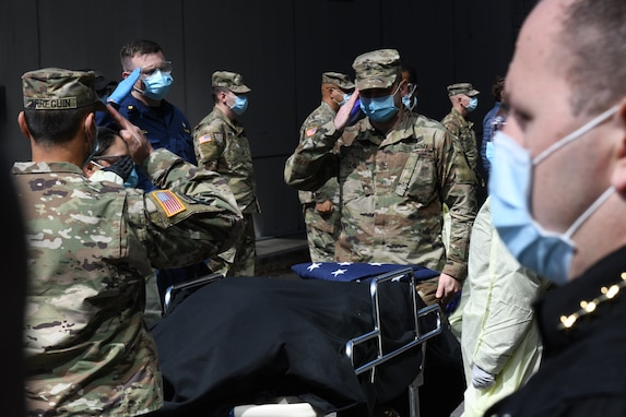 New York Army National Guard Sgt. Major Nicholas Pardi, a member of the 104th Military Police Battalion, presents an American flag during an impromptu memorial service for a  veteran who died of COVID-19 while a patient at the Javits New York Medical Station in the Jacob Javits Convention Center in New York City, April 19, 2020. (U.S. Air National Guard photo by Air Force Maj. Patrick Cordova)