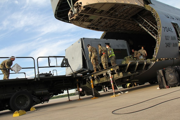 Photo shows uniformed members loading cargo from a C-5 Galaxy aircraft to the back of a truck.