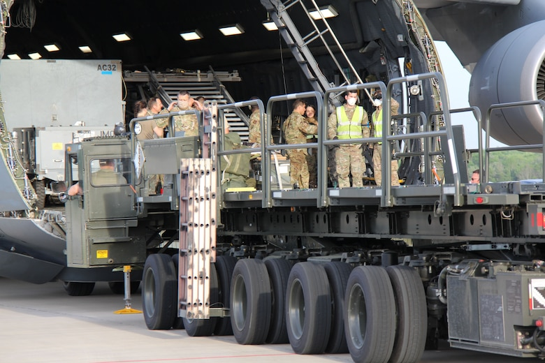 Photo shows uniformed members unloading cargo from the front end of a C-5 Galaxy aircraft.