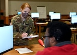 Sgt. Alexandria Tichy, a flutist with the 39th Army Band, New Hampshire Army National Guard, takes instructions from Kevin Myers, a civilian supervisor at an unemployment call center in Concord.