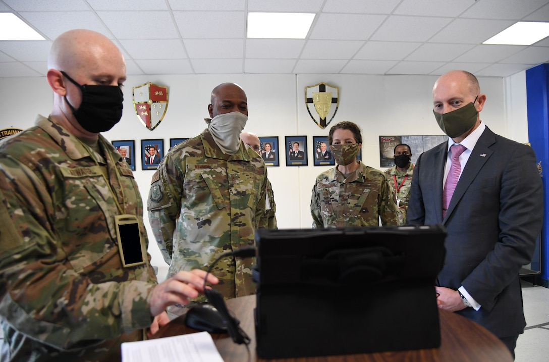 Airman briefs visitors with a laptop
