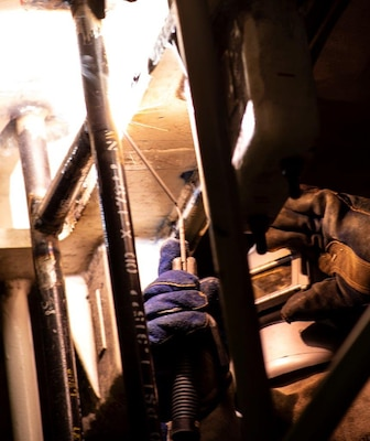 An engineer with Huntington Ingalls Industries-Newport News Shipbuilding Division welds on advanced lower stage weapons elevator aboard the aircraft carrier USS Gerald R. Ford (CVN 78), March 27, 2020. Gerald R. Ford is underway in the Atlantic Ocean conducting carrier qualifications.