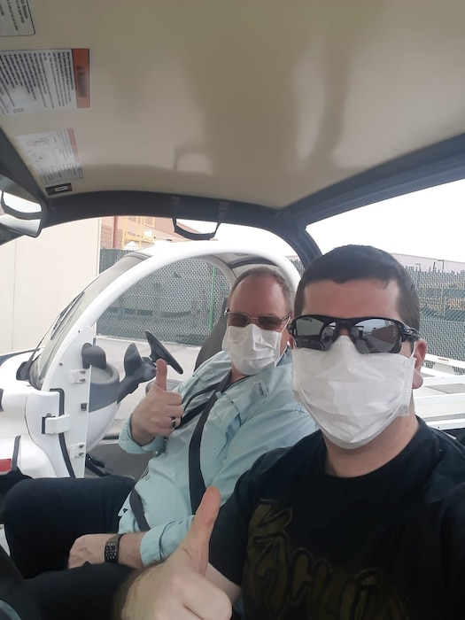Mark Wittrock, Area/Resident Engineer Bahrain and Capt. Grant Wanamaker, project manager forward, use personal protective equipment traveling to and from the office.