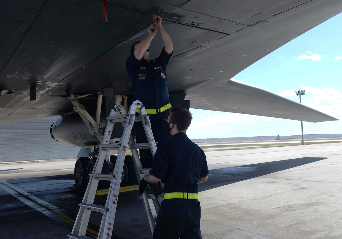 Maintainers assigned to the 28th Aircraft Maintenance Squadron fasten a panel on a B-1B Lancer at Ellsworth Air Force Base, S.D., April 22, 2020.