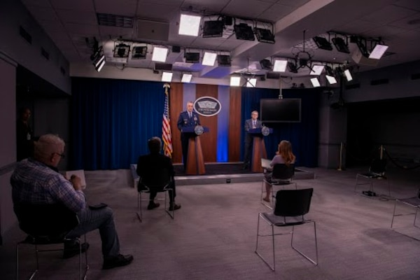 Two men speak from a stage at a news conference, with reporter seating that adheres to social distancing guidelines.