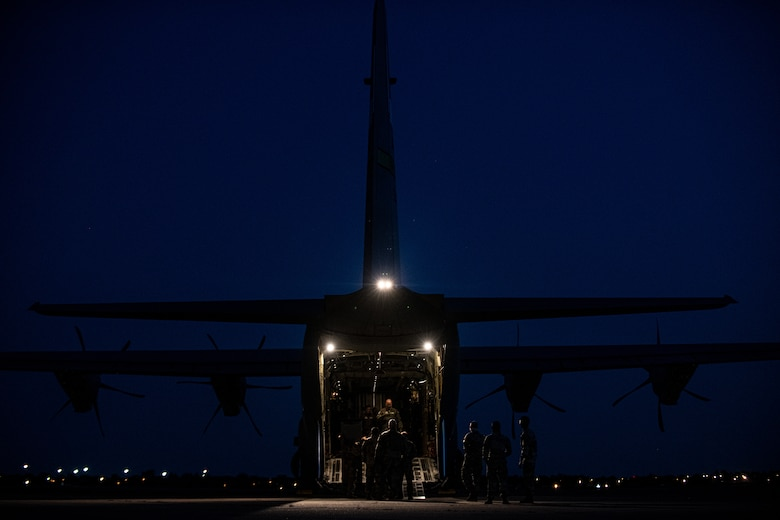 Airmen and Soldiers load cargo on a C-130J