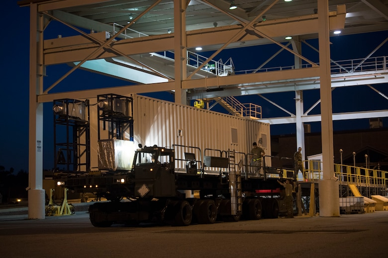 U.S. Airmen from the 437th Aerial Port Squadron use a K-Loader to move a Negatively Pressurized Conex prototype after it was delivered to Joint Base Charleston, S.C., April 21, 2020. The NPC will be tested for potential use as a transport module for individuals infected with the COVID-19 virus and other highly infectious diseases. (U.S. Air Force photo by Staff Sgt. Chris Drzazgowski)