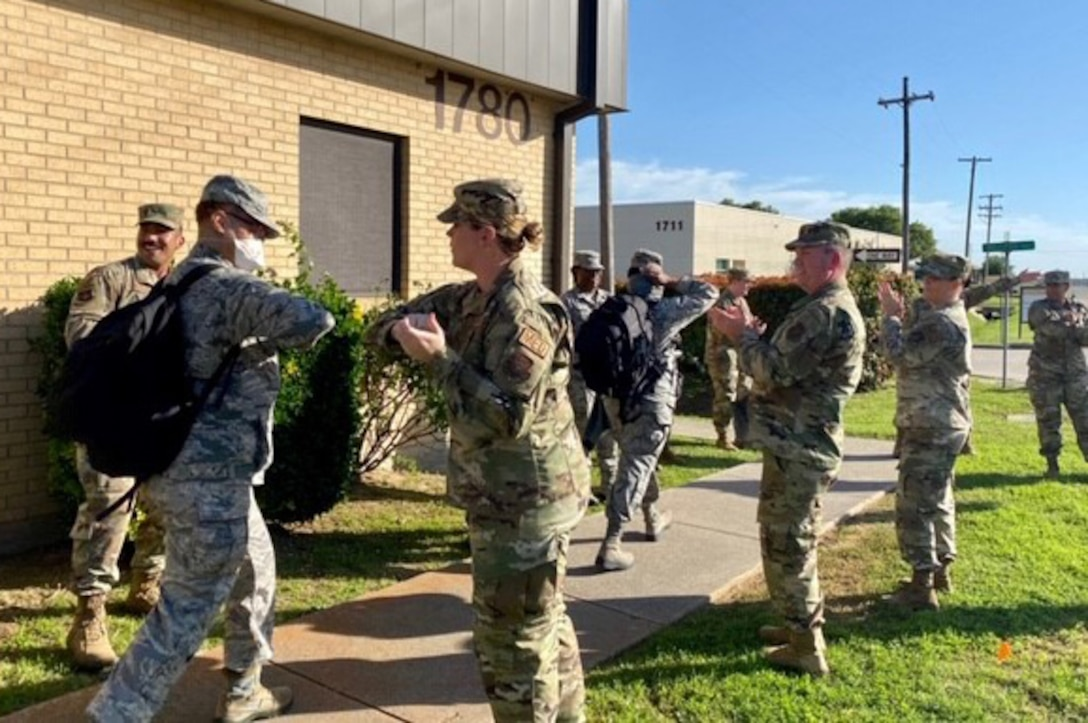 Airmen cheer on 301st Medical Squadron personnel as they prepare to depart U.S. Naval Air Station Joint Reserve Base, Fort Worth, Texas, in support of the nation's COVID-19 response on April 22, 2020. This deployment is part of a larger mobilization package of more than 770 Air Force Reservists from across the nation who are taking care of Americans fighting COVID-19. (U.S. Air Force photo by Capt. Jessica Gross)