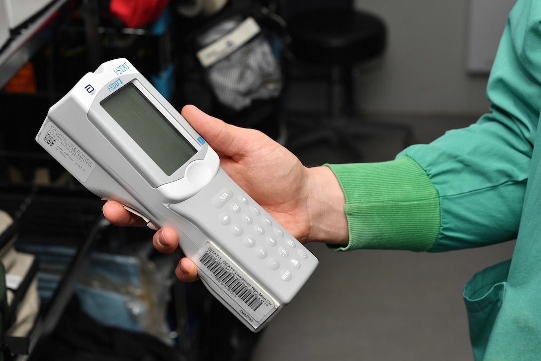 A medical worker holding a hand-held blood analyzing medical device.