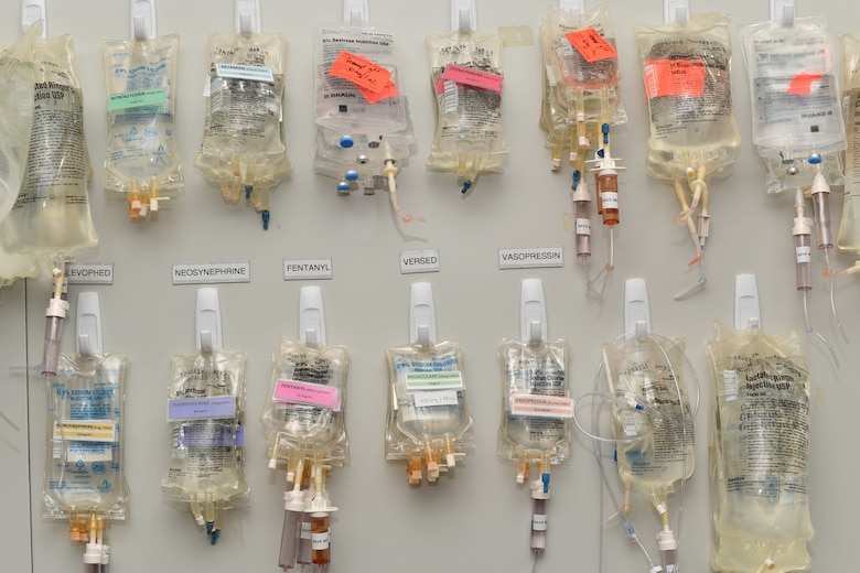 Medications in IV drip bags hang on a wall.