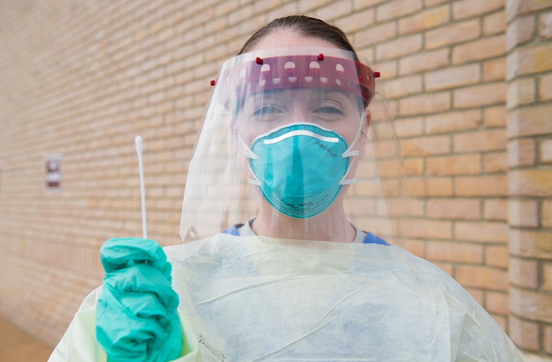 U.S. Air Force Capt. Jennifer Andrews, 423rd Medical Squadron family health clinic element chief, clinical nurse and infection preventionist, poses for a photo in a 3-D face shield as she holds a swab at a COVID-19 drive-up testing station at RAF Alconbury, England, April 13, 2020. The 423rd MDS transformed their parking lot into a drive-thru to expedite testing and prevent the spread of COVID-19. (U.S. Air Force photo by Airman 1st Class Jennifer Zima)