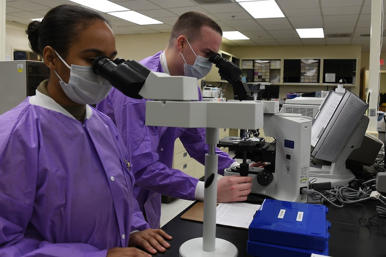 U.S. Air Force Staff Sgt. Cody Emery and Airman 1st Class Jordan Cleveland, 30th Health Care Operations Squadron laboratory technicians, conduct microscope training  at Vandenberg Air Force Base, California, April 20, 2020. Medical Laboratory Professionals Week, also known as Lab Week, is observed annually to promote awareness and show appreciation to medical laboratory professionals and pathologists for the work they do to assist patients. (U.S. Air Force photo by Staff Sgt. Brittany E. N. Murphy)