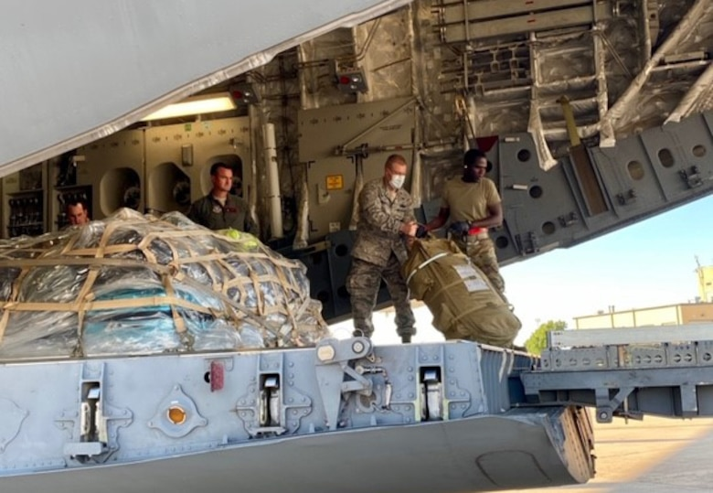 301st Fighter Wing Commander, Col. Allen Duckworth, second from right, helps to load luggage of deploying Airmen aboard a C-17 Globemaster III at U.S. Naval Air Station Joint Reserve Base, Fort Worth, Texas on April 22, 2020. This deployment is part of a larger mobilization package of more than 770 Air Force Reservists from across the nation who are taking care of Americans fighting COVID-19. (U.S. Air Force photo by Capt. Jessica Gross)